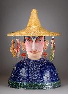 Ceramic Sculpture of Chinese Kitchen God with food items hanging from hat, created by ceramic sculptor Antonia Lawson